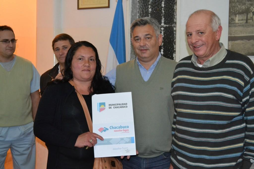 La señora Isabel Melo recibe la escritura de su vivienda en manos de Barrientos y Micucci.