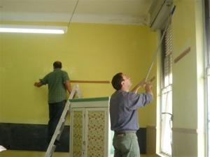 Padres de alumnos realizando trabajos de pintura en una de las aulas.