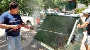 Juan Coliqueo realizando tareas de lavado de contenedores de residuos.
