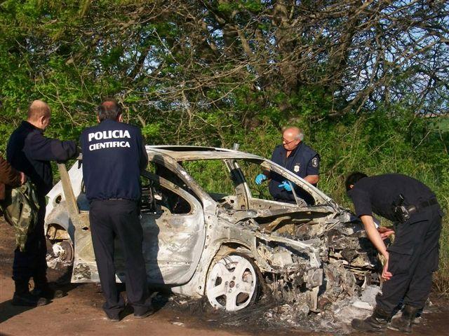 Los peritos trabajando sobre el Peugeot 307 destruido por el fuego.