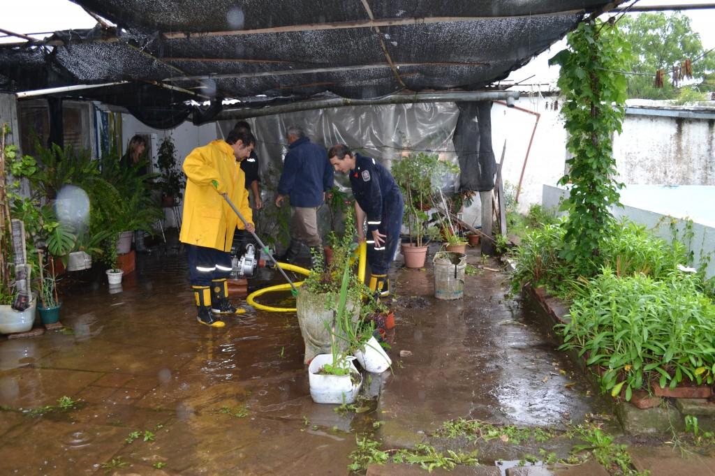Bomberos Voluntarios trabajando en una de las viviendas damnificadas por el agua.