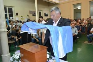 Barrientos coloca una Bandera Argentino sobre la urna junto a la hermana de Pepe.