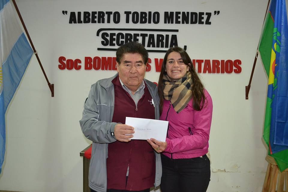 El Dr. Valdivia recibe su premio en manos de Florencia Papini.