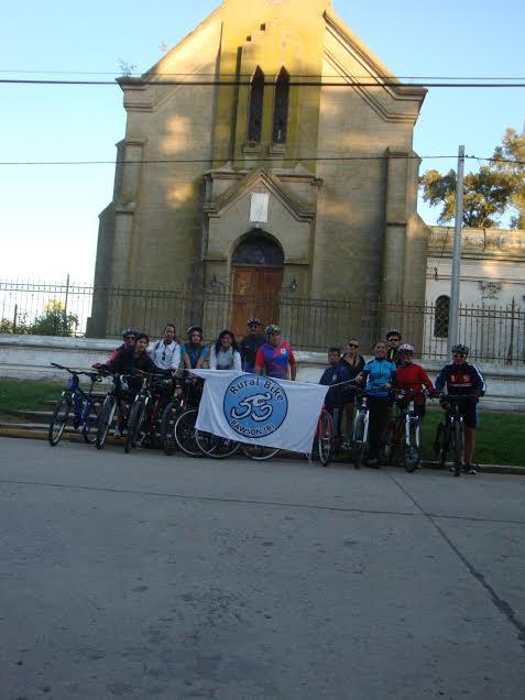 Los ciclistas antes de partir de Rawson. De fondo, La Iglesia Inmaculada Concepción.
