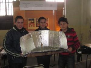 Félix Rubiolo, Martín Ojeda y Gastón Micucci mostrando la cocina solar. Foto gentileza: Pablo Pastore.