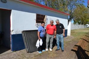 Walter Fernández, Edgardo Ibarrondo y Pedro Saldañez y detrás, las rejas donadas al Club San Lorenzo.