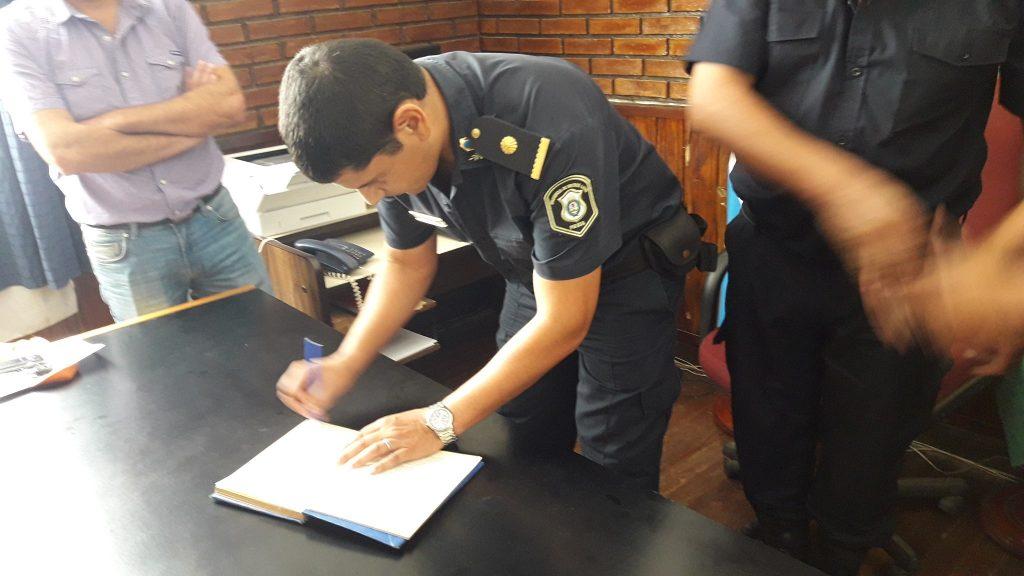 El Subcomisario, Elías Montiel, procede a firmar el libro.