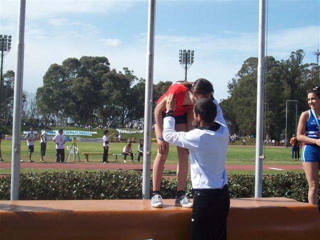 Irina recibe la medalla de oro en manos de su entrenador el profesor Marcelo Millán.