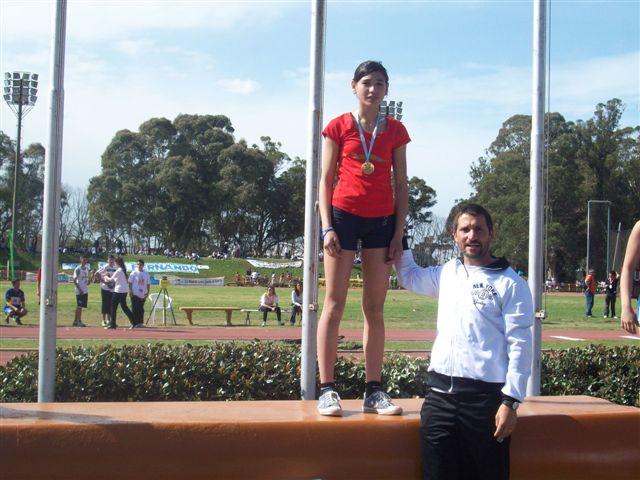 Irina luego de recibir la medalla de oro junto a su entrenador el profesor Marcelo Millán.