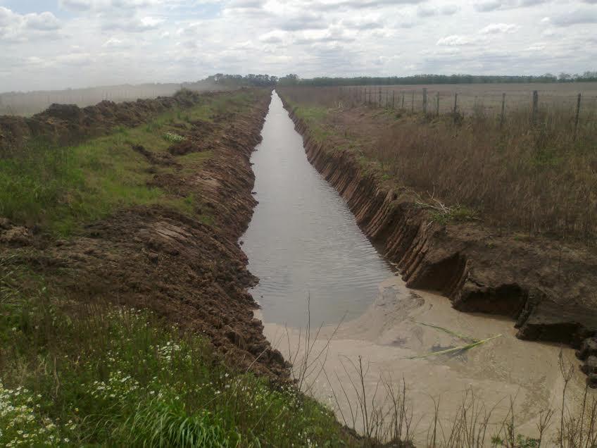 Limpieza de canal que corre a la vera de la Ruta 32.