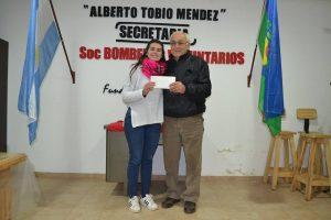 Roberto Estévez recibe el premio en manos de Florencia Papini.