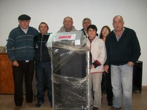 Fernando Richini, el tercero desde la izquierda, recibiendo su premio por pago contado. A su lado miembros de Comisión Directiva de Bomberos y el Bombero Catalino Fernández, quién vendió la boleta ganadora de la cinta de caminar.