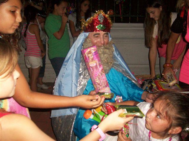 Melchor entregando juguetes a los niños.