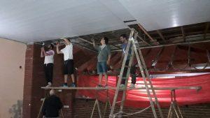 Miembros de comisión directiva trabajando en la colocación del nuevo cielorraso.