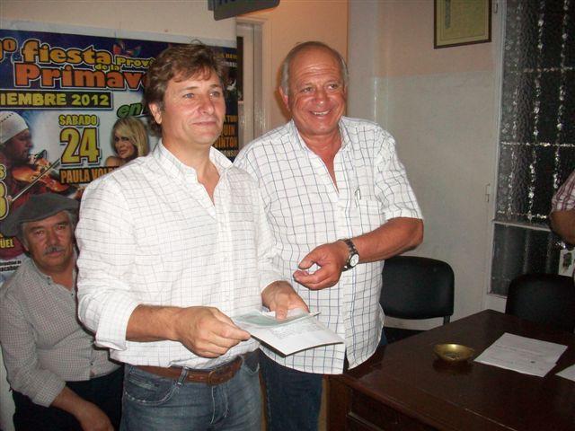 El presidente de la Fiesta de la Primavera recibe subsidio en manos de Micucci.