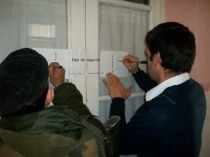 El Sargento Romero y Sebastián Viegas del correo Argentino colocando y firmando las fajas de seguridad.