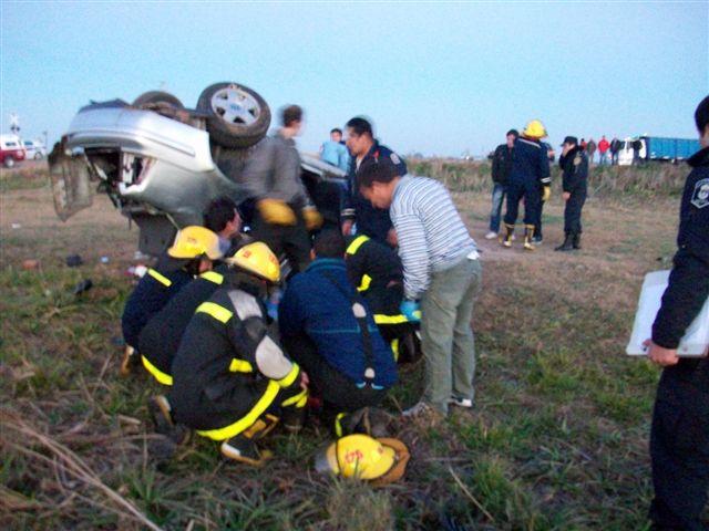 Bomberos de Rawson terminado de retirar del interior del Bora a uno de los jóvenes accidentados.