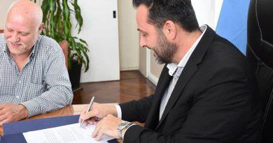 Aiola firmando convenio