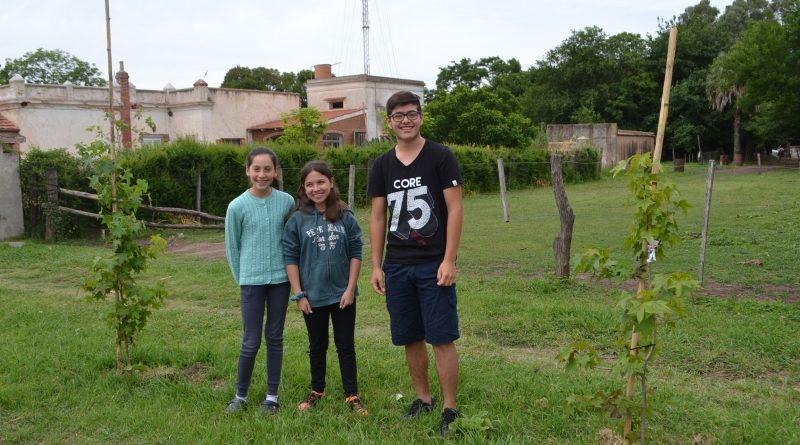 Alumnos junto a árboles plantados