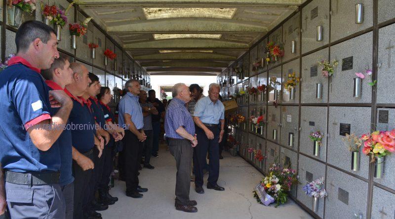 Momento en que colocan palma en tumba de Roberto Ostolaza, primer presidente de comisión de Bomberos