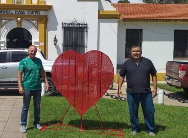 Gerardo Pedretti y el director del centro asistencial, Dr. Marcos Umerez, en la colocación del Corazon Reciclador de tapitas de gaseosas